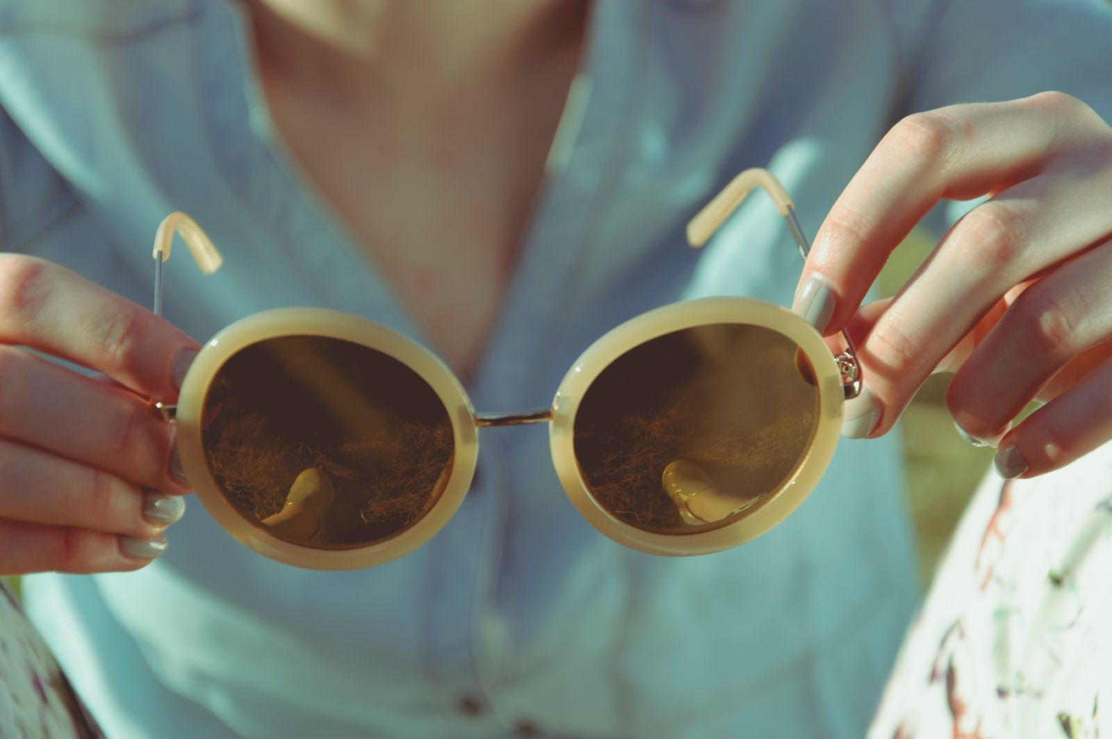 Woman holding sunglasses image